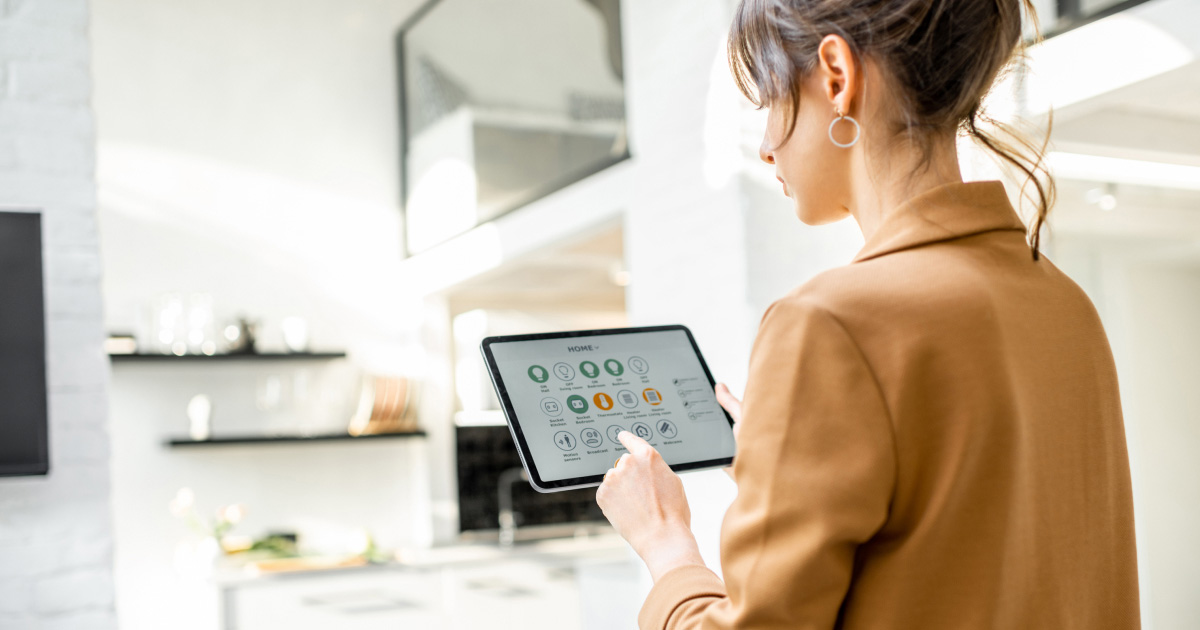 Young woman utilising smart home features from tablet in the kitchen
