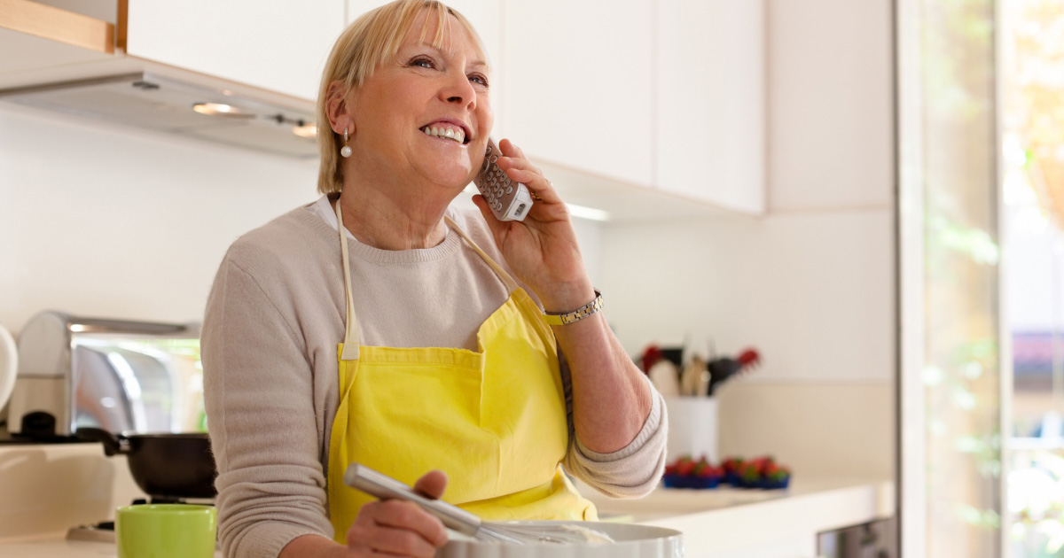 Close up of woman cooking while having a call in the kitchen