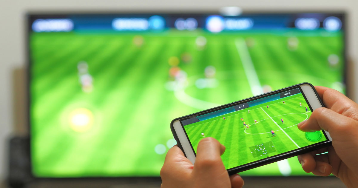 Close up of football ground on TV and on a smartphone